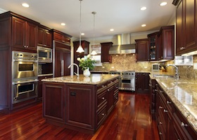 Kitchen in luxury home with cherry wood cabinetry matching the hardwood flooring