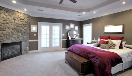 Interior of a large modern bedroom with a fireplace and ceiling fan. Horizontal format.