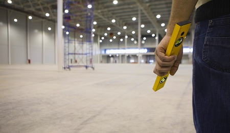 Midsection of manual worker holding spirit level in empty warehouse