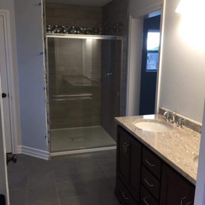 Bathroom Featuring a Walk In Shower with Decorative Tile and Slate Tile Flooring